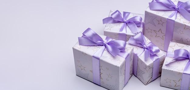 Geschenkboxen aus elegantem papier mit lila bändern auf lila hintergrund. schöne ferien.