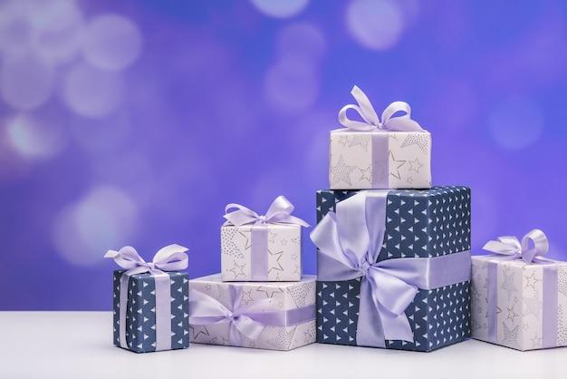 Geschenkboxen aus intelligentem papier mit lila bändern auf weiß.