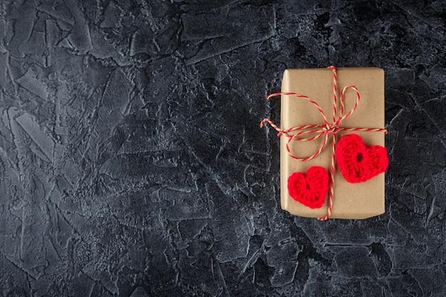 Geschenkboxen aus kraftpapier und dekorativ gehäkelten herzen. valentinstagflach lag. draufsicht.