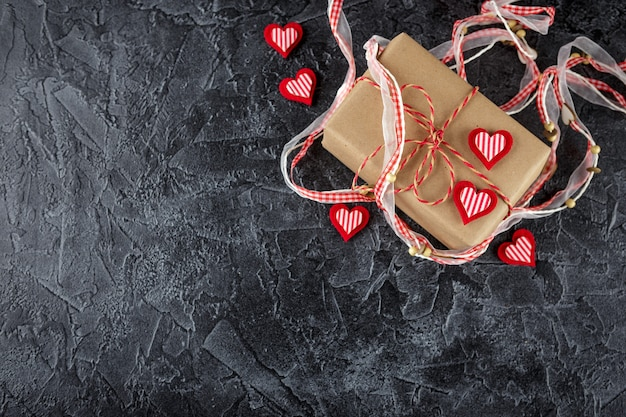 Geschenkboxen aus kraftpapier, zierband mit holzherzen und zierfilzherzen. valentinstag. flach liegen. draufsicht.