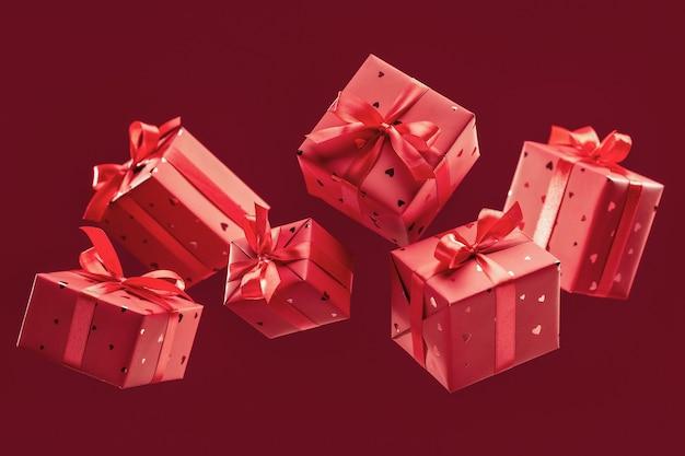 Geschenkboxen aus rotem papier mit satinbändern und schleifen