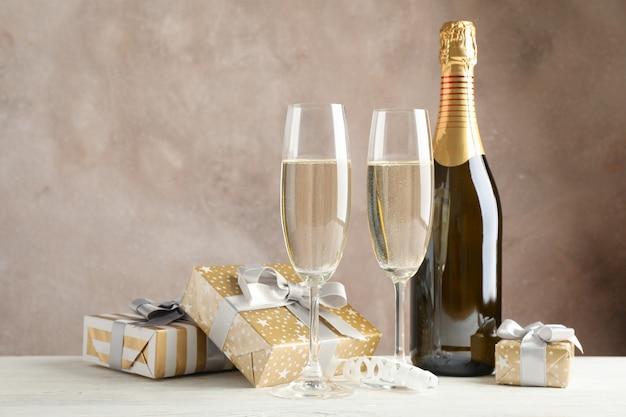 Geschenkboxen, champagnergläser und flasche gegen braunen raum, platz für text