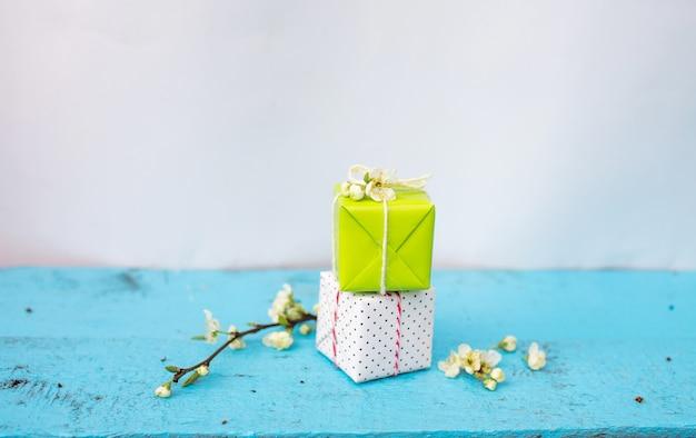 Geschenkboxen der weißen und hellgrünen farbe auf einem blauen frühlingshintergrund, frühlingsblumen. frühlingszusammensetzung.