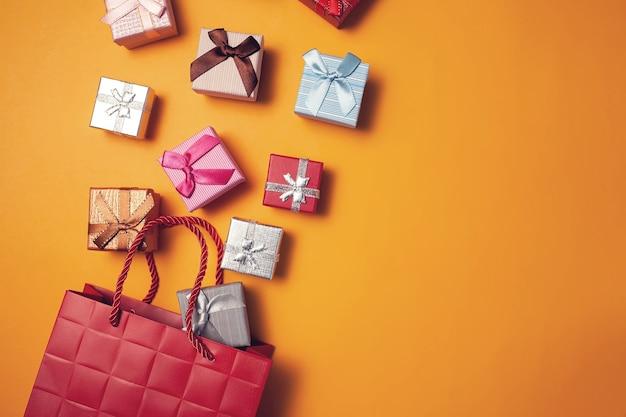 Geschenkboxen, die in geschenktüte auf gelbem hintergrund fallen. feier-, party- und shopping-konzept