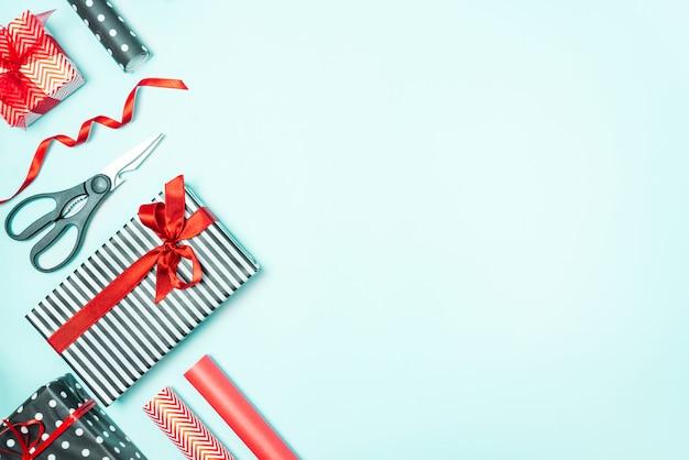 Geschenkboxen, eingewickelt in schwarz-weiß gestreiftes und rotes papier mit verpackungsmaterialien über einem blauen hintergrund. vorbereitung der weihnachtsgeschenke.