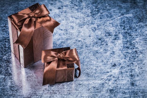 Geschenkboxen eingewickelt in zerknittertes glitzerndes papier auf zerkratztem metallischem hintergrund