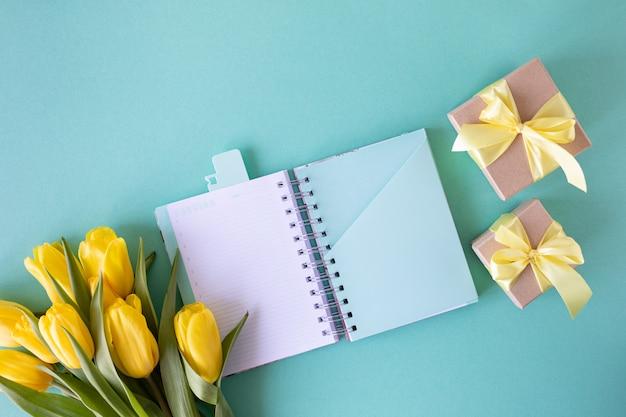 Geschenkboxen, gelbe tulpen und ein notizbuch