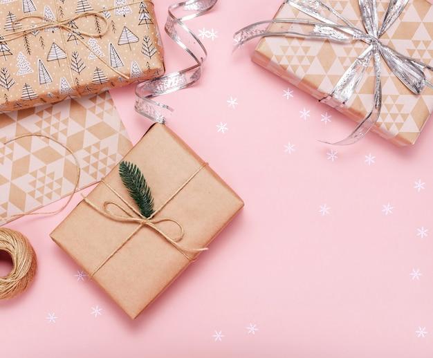 Geschenkboxen im kraftpapier auf rosa hintergrund. flach liegen. kopieren sie platz.