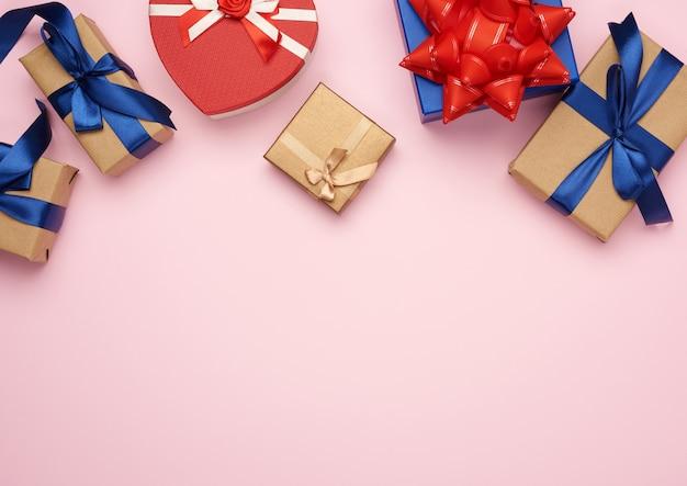 Geschenkboxen in braunem papier eingewickelt und mit einer roten und blauen schleife gebunden