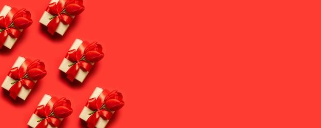 Geschenkboxen in buntes papier gewickelt und mit schleifen auf rot gebunden.