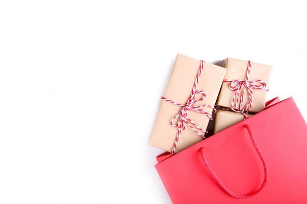 Geschenkboxen in der roten papiertüte lokalisiert