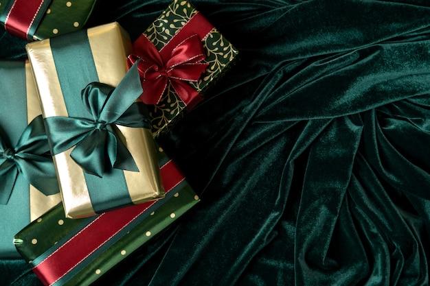 Geschenkboxen in goldpapier mit gezeitengrünen satinbändern
