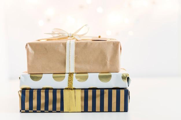 Geschenkboxen in sweetie-papieren in der nähe von lichterketten