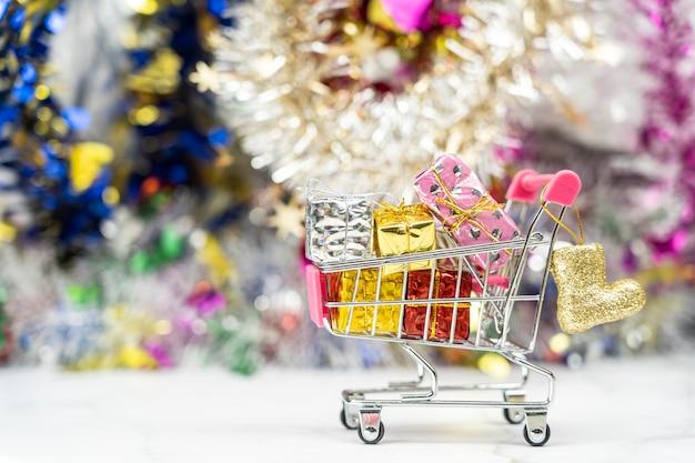 Geschenkboxen, kleiner supermarkt-einkaufswagen voller geschenke für neujahrs- oder geburtstagskonzept