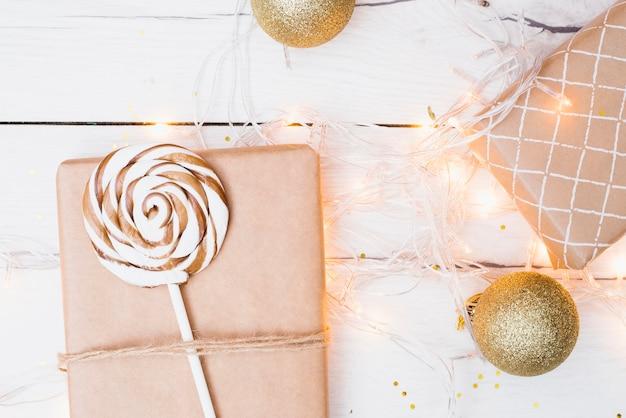 Geschenkboxen, lutscher und weihnachtskugeln in der nähe von beleuchteten lichterketten