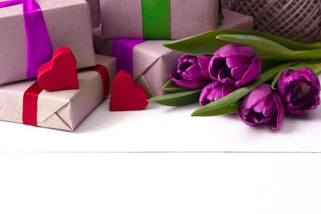 Geschenkboxen mit blumen auf weißer holzwand