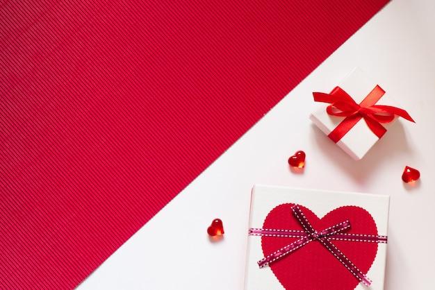 Geschenkboxen mit bögen und herzen auf rotem und weißem hintergrund. kreatives denken an liebe und valentinstag