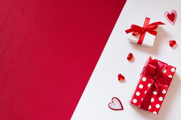 Geschenkboxen mit bögen und herzen auf rotem und weißem hintergrund.
