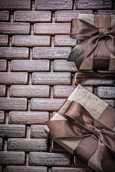 Geschenkboxen mit braunen bändern auf holzmatten-feiertagskonzept verpackt