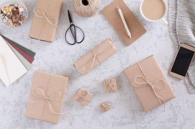 Geschenkboxen mit einem kraftpapier auf weißer strukturierter tabelle, draufsicht und ebenenlage