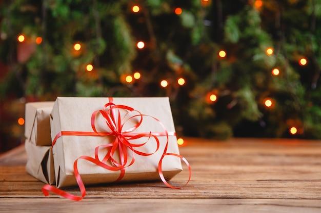 Geschenkboxen mit einer großen roten schleife aus funkelnden partylichtern. weihnachtsgeschenk.