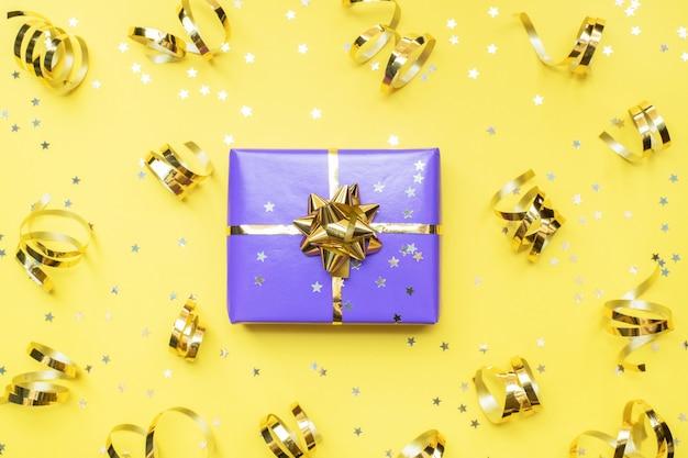 Geschenkboxen mit goldbändern und bögen, konfettisterne auf einem gelben hintergrund. textfreiraum flach legen. grußkarte für geburtstagsfeier, weihnachten hochzeit muttertag.