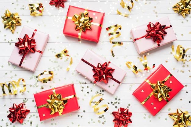 Geschenkboxen mit goldbändern und bögen, konfettisterne auf einem weißen hintergrund. textfreiraum flach legen. grußkarte für geburtstagsfeier, weihnachten hochzeit muttertag.