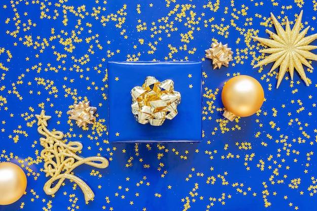 Geschenkboxen mit goldenem bogen und tannenbaum mit weihnachtskugeln auf blauem grund, golden glänzende glitzersterne auf blauem hintergrund