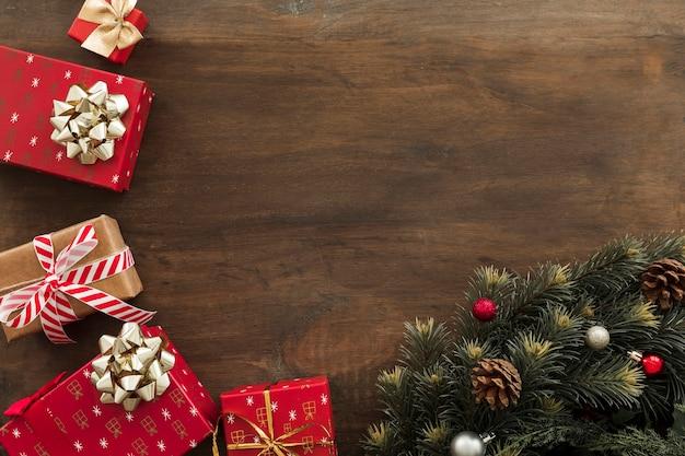 Geschenkboxen mit grünen tannenbaumasten auf tabelle