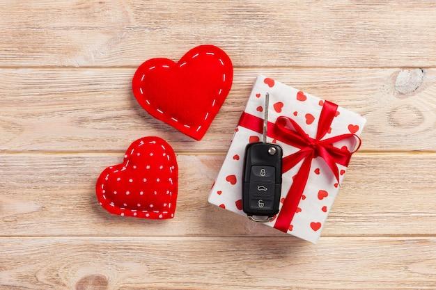 Geschenkboxen mit herzpackpapier und autoschlüsseln auf holz