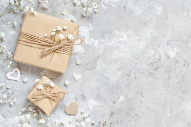 Geschenkboxen mit kleinen weißen blumen und herzen auf grauem hintergrund