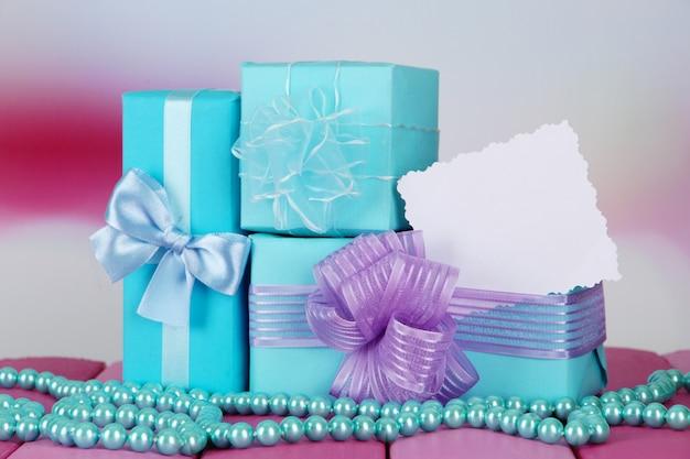 Geschenkboxen mit leerem etikett und rosenkranz auf dem tisch auf hellem hintergrund