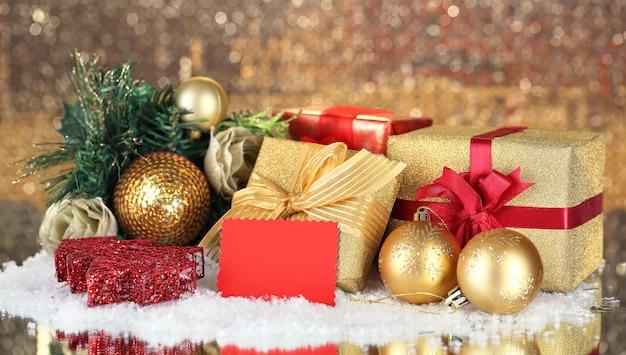 Geschenkboxen mit leerem etikett und weihnachtsschmuck auf dem tisch auf hellem hintergrund