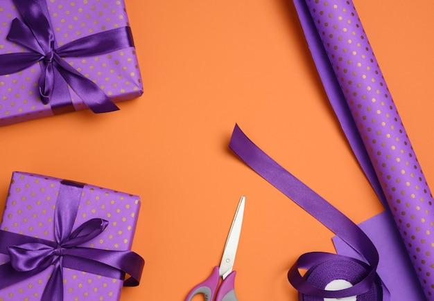 Geschenkboxen mit lila seidenband auf orangem hintergrund, ansicht von oben gebunden. festliche kulisse, flach