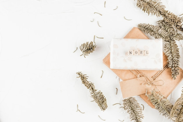 Geschenkboxen mit noel-titel zwischen nadelzweigen