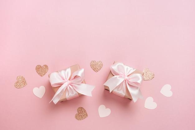 Geschenkboxen mit rosa band und herzen auf pastellrosa hintergrund.