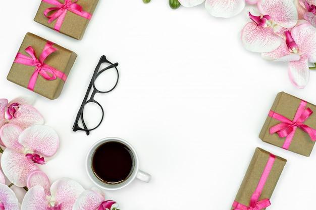 Geschenkboxen mit rosa band und orchideenblumen lokalisiert