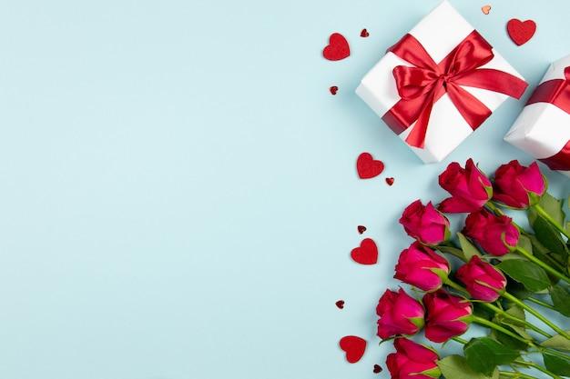 Geschenkboxen mit rotem band, rosen und herzkonfetti auf pastellblauer oberfläche