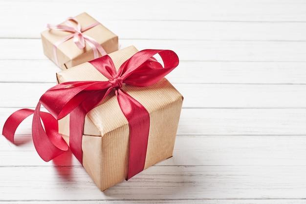 Geschenkboxen mit rotem bogen auf einem weißen hintergrund, kopienraum