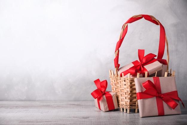 Geschenkboxen mit roten bändern auf einem korb