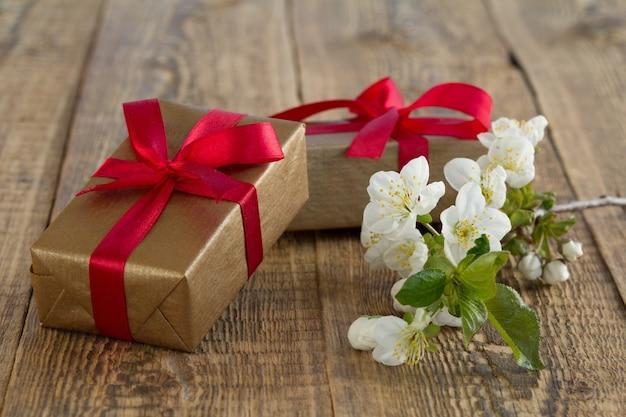 Geschenkboxen mit roten bändern umwickelt mit jasminblüten auf holzbrettern. farbton geändert.