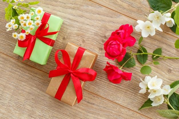 Geschenkboxen mit roten bändern und schönen rosen- und jasminblüten auf dem holzhintergrund. konzept, an feiertagen ein geschenk zu machen. ansicht von oben.