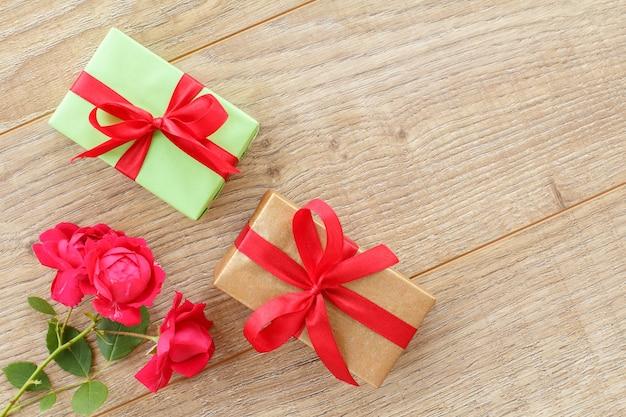 Geschenkboxen mit roten bändern und schönen rosenblüten auf dem holzhintergrund. konzept des schenkens an feiertagen. ansicht von oben.