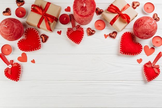 Geschenkboxen mit roten kerzen auf dem tisch