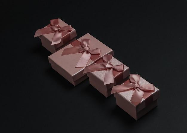 Geschenkboxen mit schleife auf schwarzem hintergrund. komposition für weihnachten, black friday, geburtstag oder hochzeit.