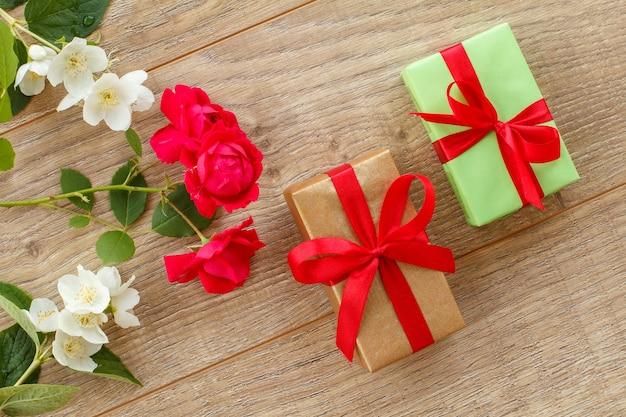 Geschenkboxen mit schönen rosen- und jasminblüten auf dem holzhintergrund. konzept, an feiertagen ein geschenk zu machen. ansicht von oben.
