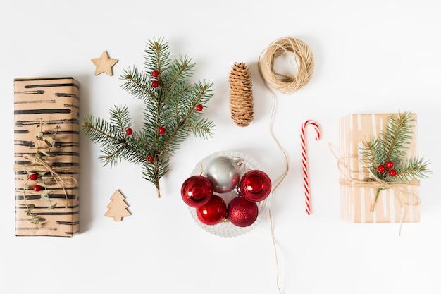 Geschenkboxen mit tannenbaumzweig und glänzenden kugeln