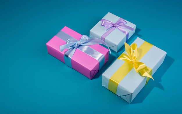 Geschenkboxen mit verschiedenen farben auf einer bannerschablone. blaue geschenkbox und gelbe schleife gegen kühnen blauen hintergrund.
