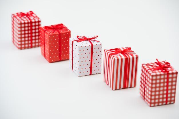Geschenkboxen mit weihnachtsgeschenken eingewickelt im roten papier mit verzierung auf weißem hintergrund