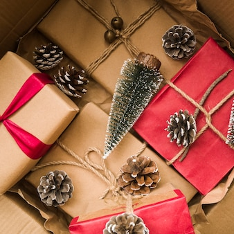 Geschenkboxen nahe tannenzweigen in der pappschachtel
